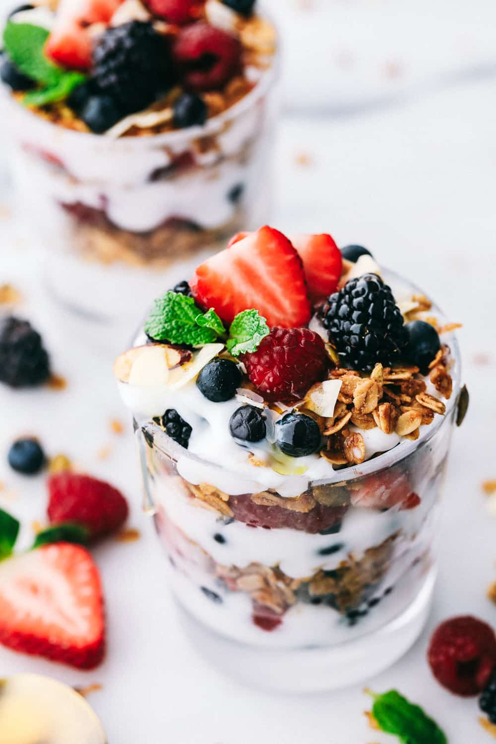 yogurt parfaits layered in glass cups garnished with mint and berries spread around the glass cups for display.