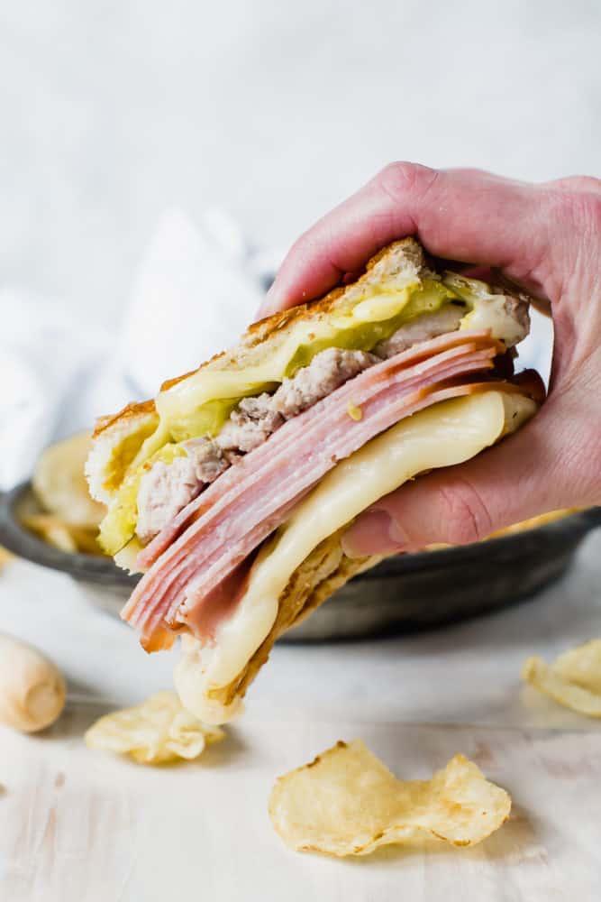 hand holding cuban sandwich