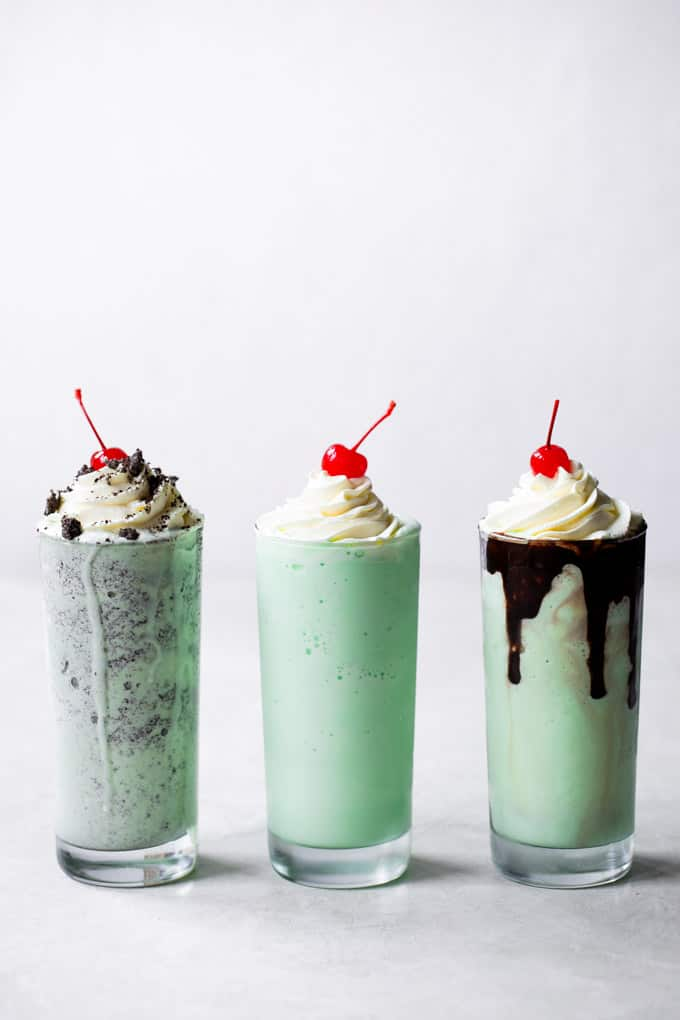 Three tall glasses of shamrock milkshake with whip cream and a cherry on top of each of them.