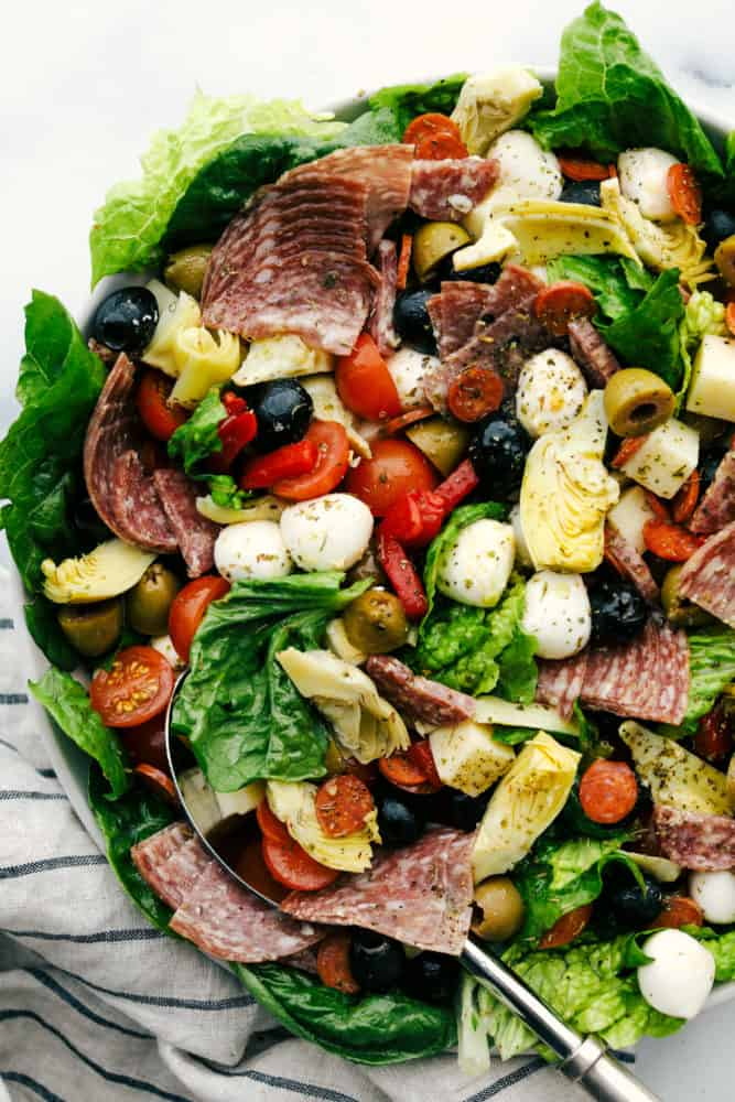 Antipasto salad with slices of meat, sliced cherry tomatoes, cheese balls, green and black olives and lettuce all in a bowl with a metal spoon.