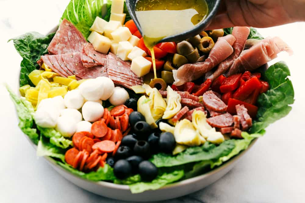 Antipasto salad with the lemon olive oil dressing being poured over top.