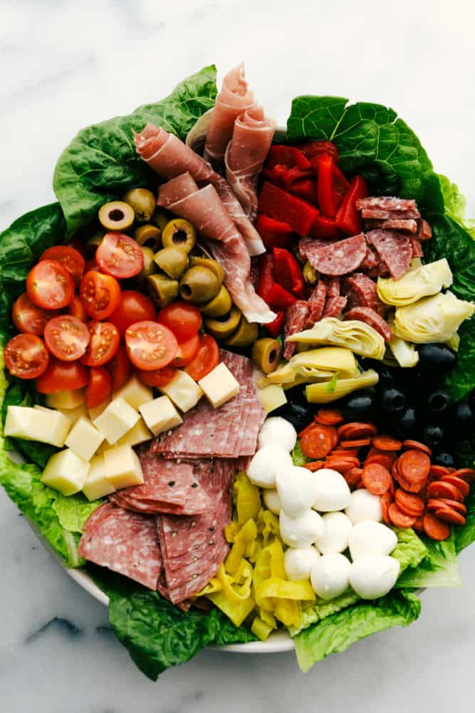 Antipasto salad with the ingredients spread out over the salad into sections.