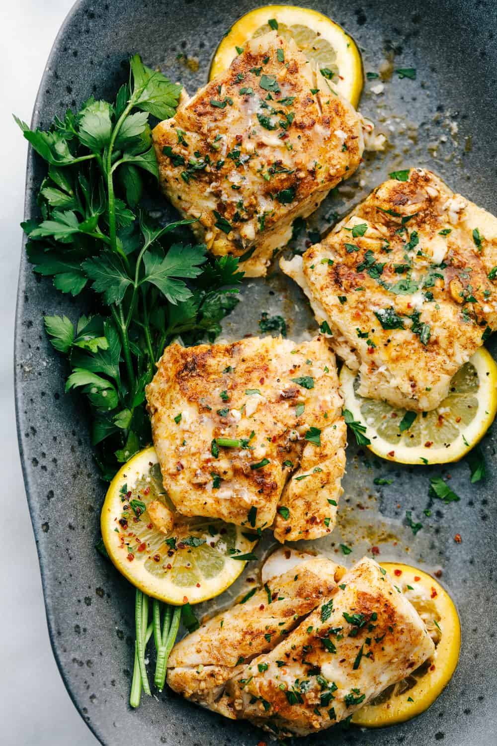 Baked cajun garlic butter cod served on a black speckled plate with green garnish and lemon slices underneath the cod filets.