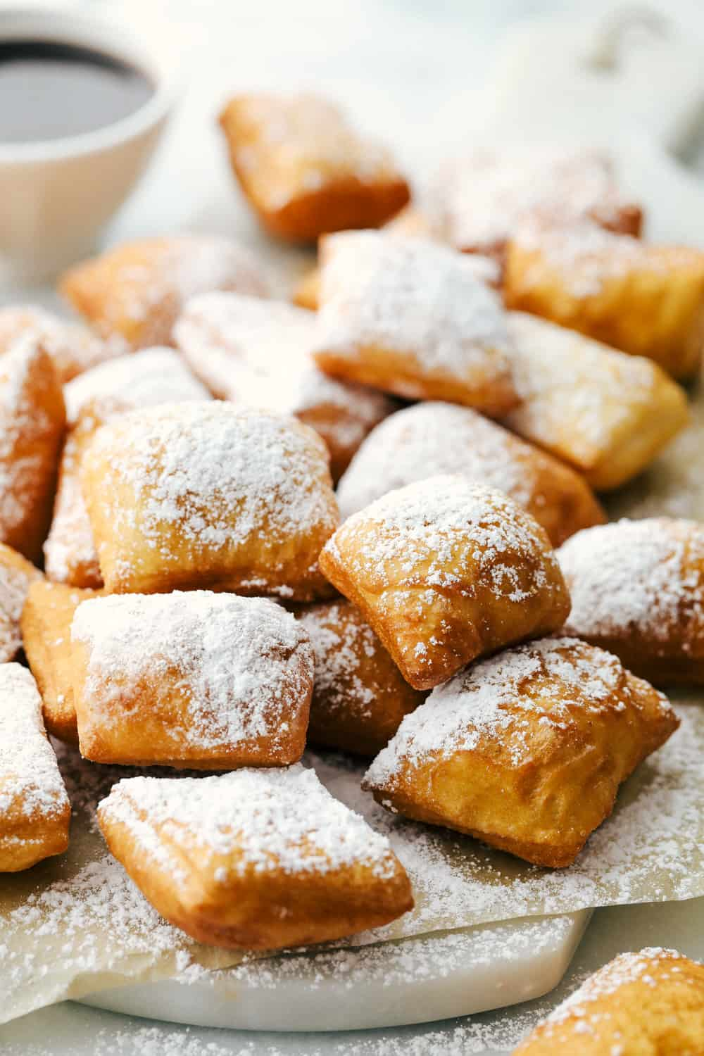 Several beignets on a cutting board sprinkled with powder sugar and chocolate syrup on the side.