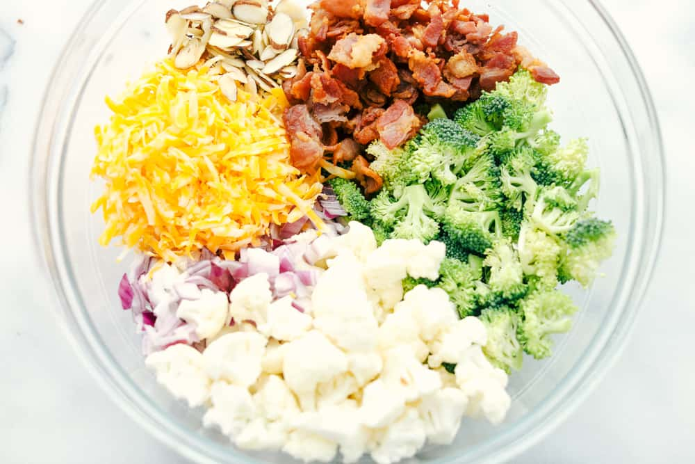 Shredded cheese, sliced almonds, bacon chopped up, broccoli and cauliflower florets and red onion chopped up separated in a glass bowl.