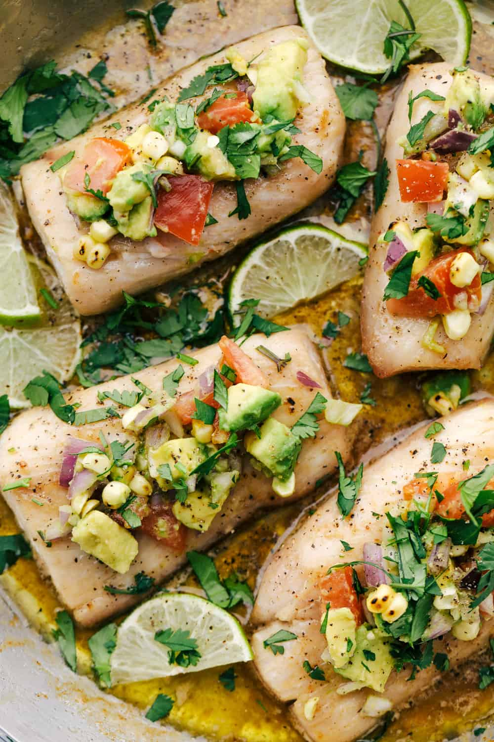 Mahi Mahi filets ina skillet with the brown butter sauce and garnished with avocado salsa with lime wedges in the skillet.