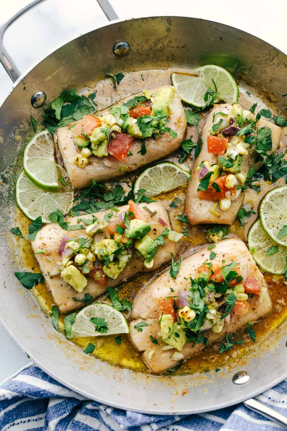 Mahi Mahi filets cooked in a skillet with brown butter and garnished with avocado on top.