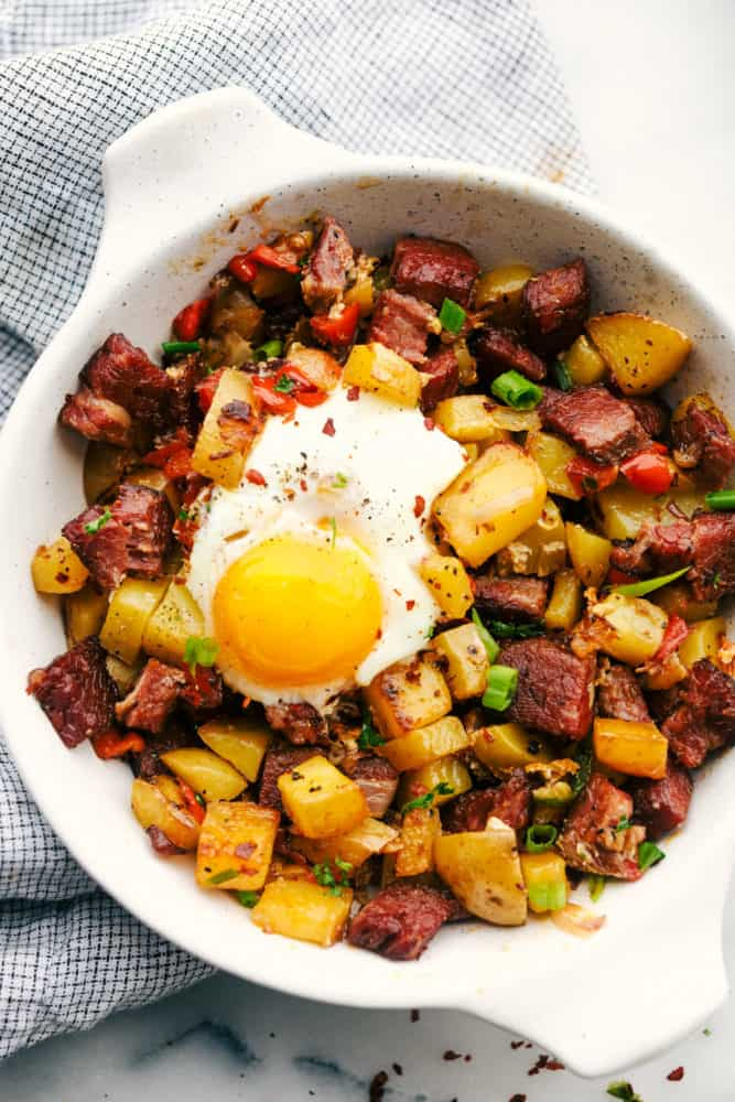 Corned beef hash with an egg on top in a white skillet.