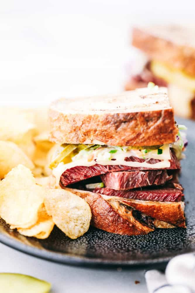 Corned beef sandwich on a plate with potato chips on the side.