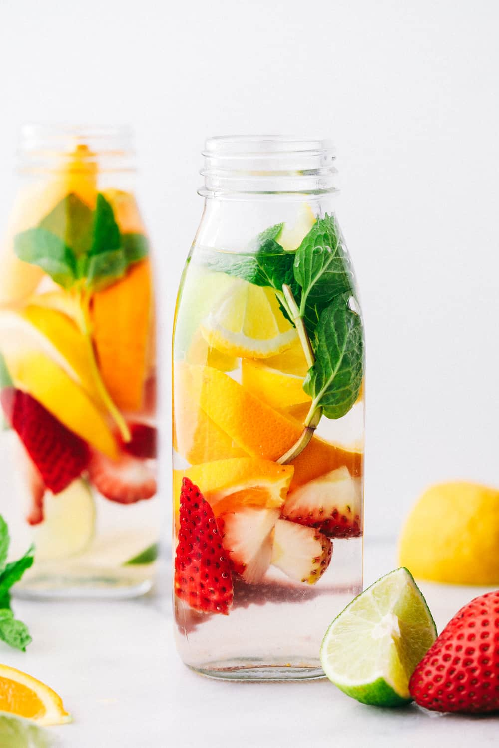 Detox water in a glass jar filled with lemon, limes, strawberries and mint.