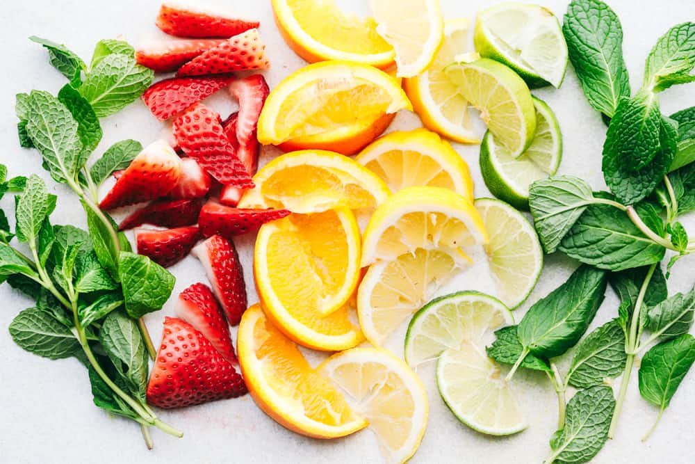 Photo filled with a mint, sliced strawberries, quartered oranges, lemons and limes with another side of mint on a table.