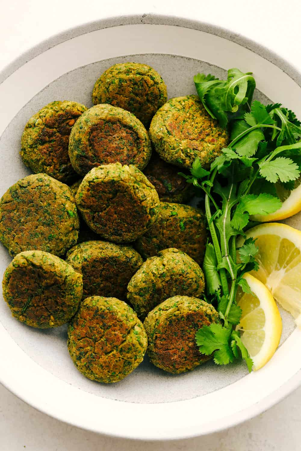 Falafel on a plate with lemon as a garnish and cilantro.