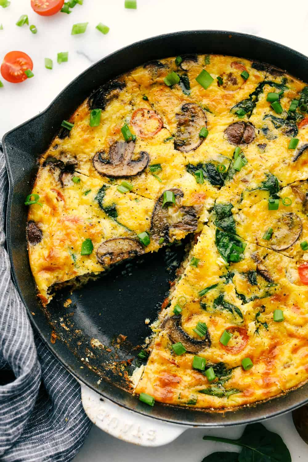 Breakfast frittata cooked on a skillet with a slice of frittata missing off of it.