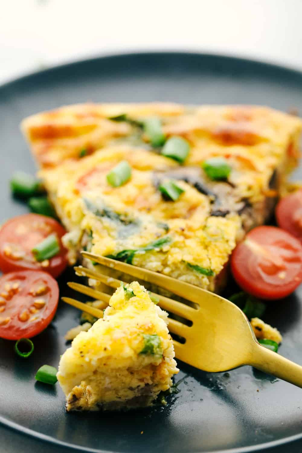 Breakfast frittata on a plate with a piece cut off with cherry tomatoes sliced on the side.