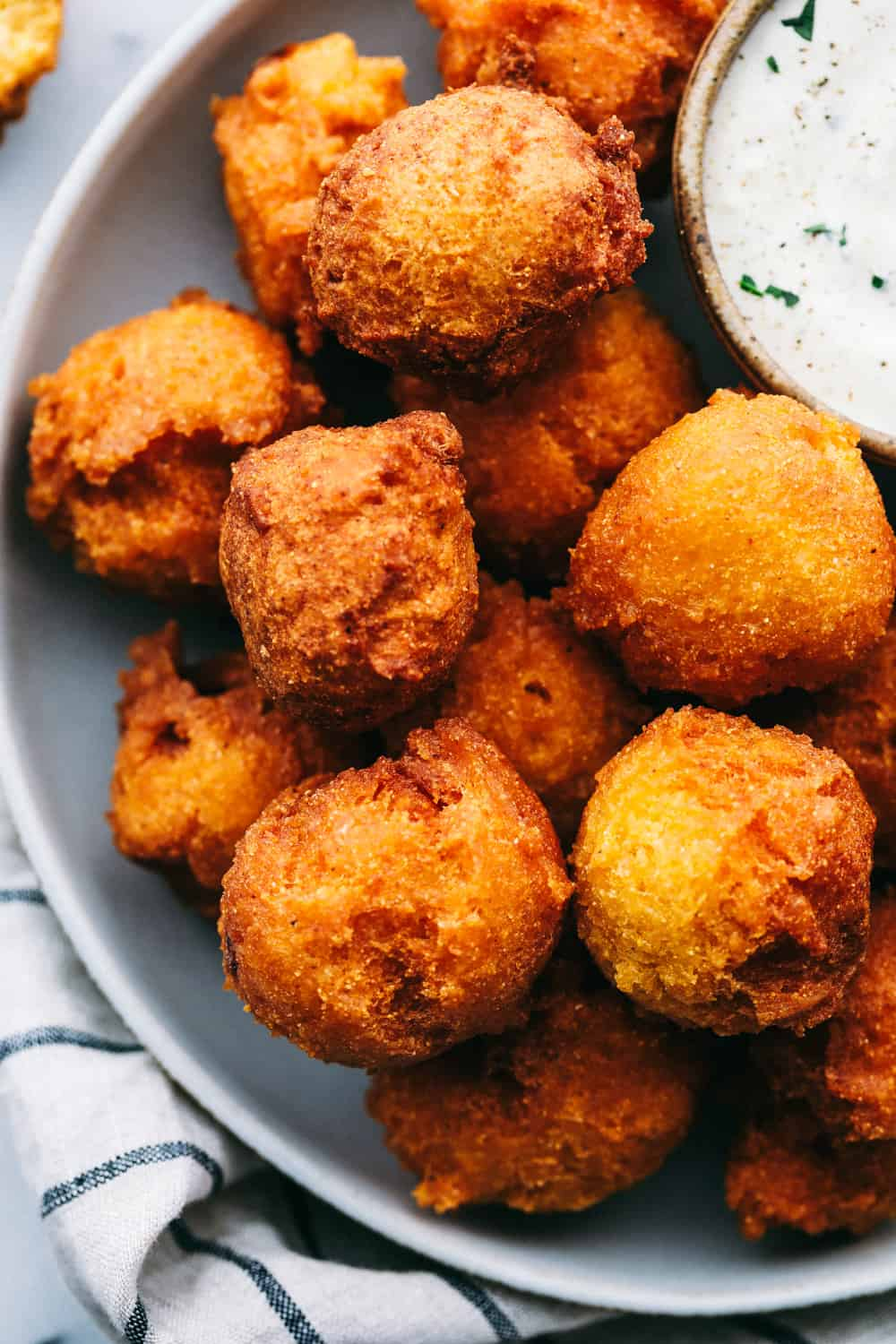 Hush puppies on a plate with a side of tartar sauce.