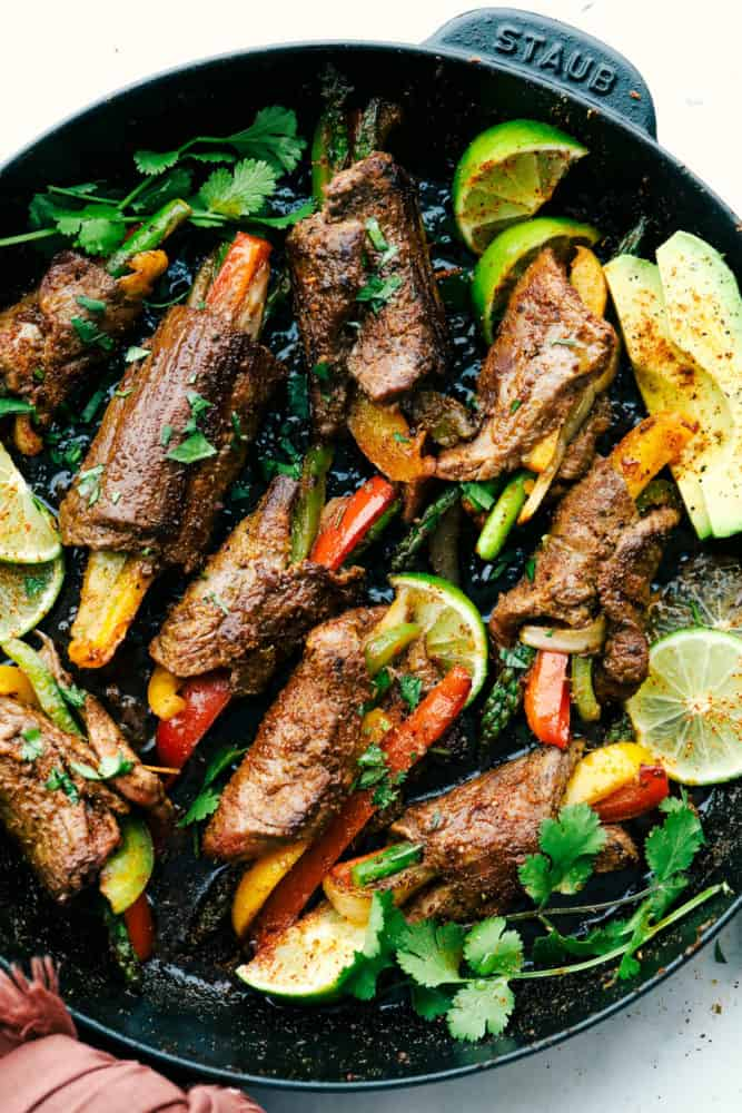 Steak fajita roll ups on the skillet being cooked with lime wedges and cilantro around the skillet for garnish.
