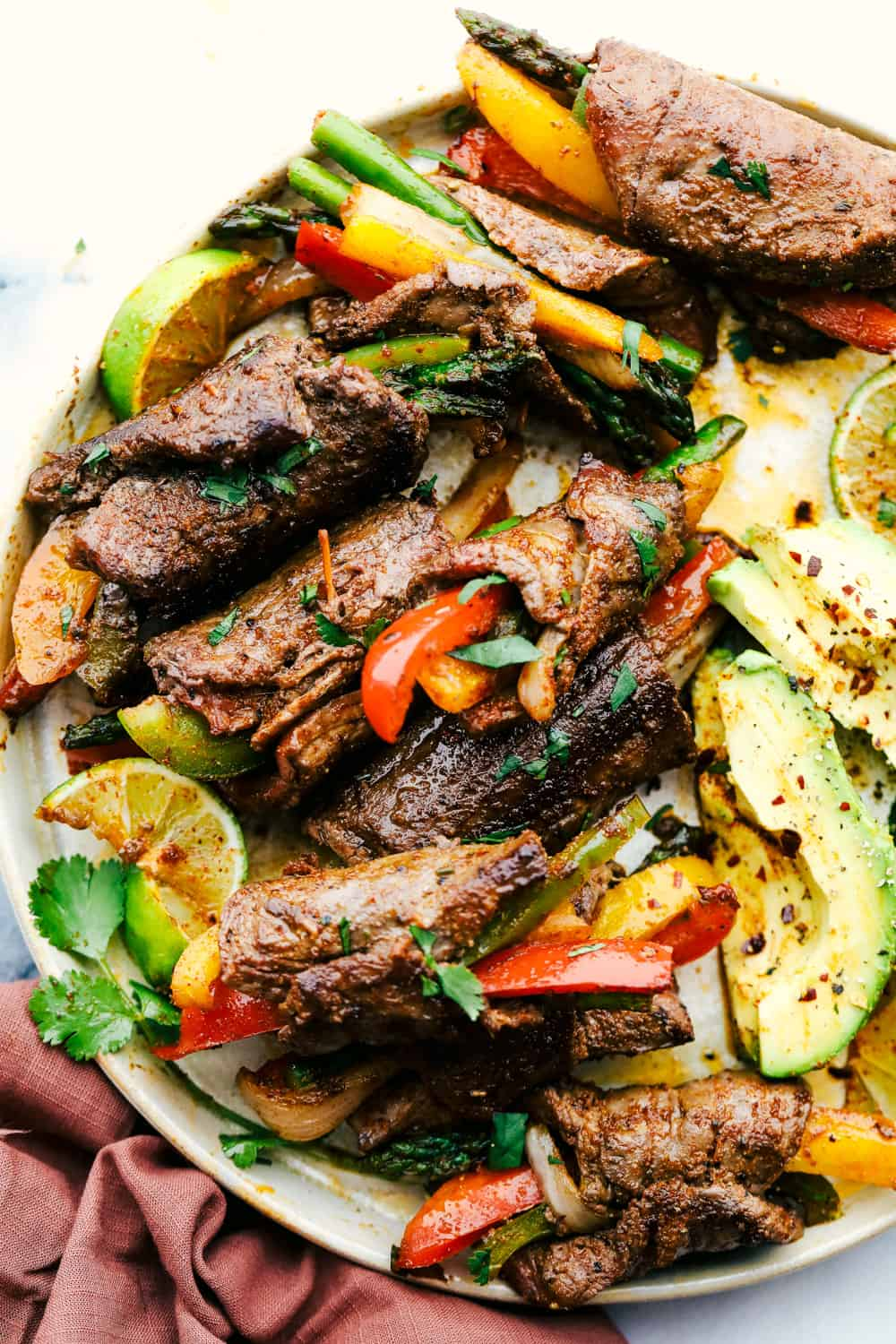 Bell peppers and asparagus wrapped up in flank steak with avocados on a plate.
