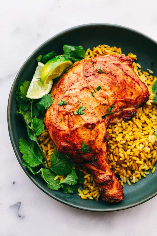 Cooked Tandoori chicken on a black plate with leaves and lime wedges on the left side and rice on the right side.