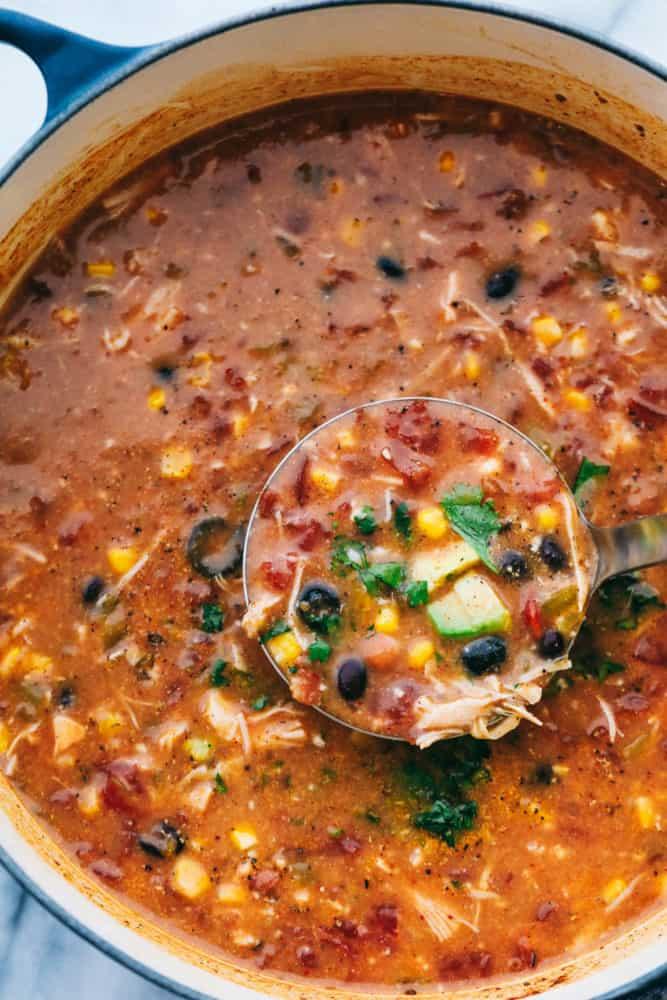 Tous les 8 boîtes d'ingrédients dans la soupe de poulet taco cuisson dans une casserole avec une louche montrant les ingrédients de cuisson ensemble.