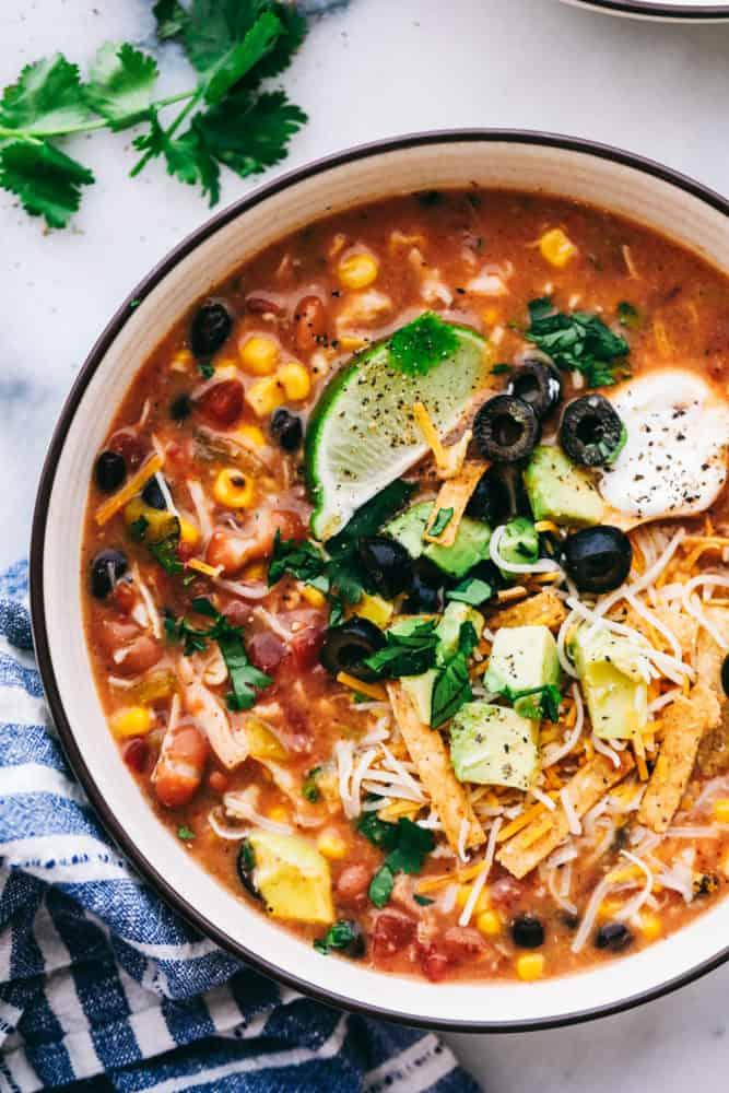 Un bol de 8 boîtes de soupe de taco au poulet garni de quartiers de lime, de crème sure, d'olives tranchées, d'avocat et de lanières de tortilla.