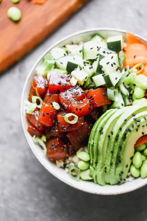 A complete poke bowl with ahi tuna, zucchini, avocado, edamame and sliced carrots.