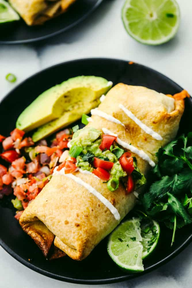 Chicken chimichanga on a black plate with an avocado sliced and limes slices on the side.