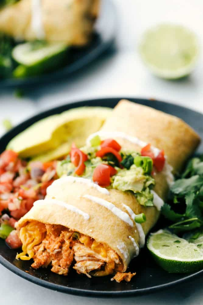 Chicken chimichanga on a plate with salsa, avocado and limes.