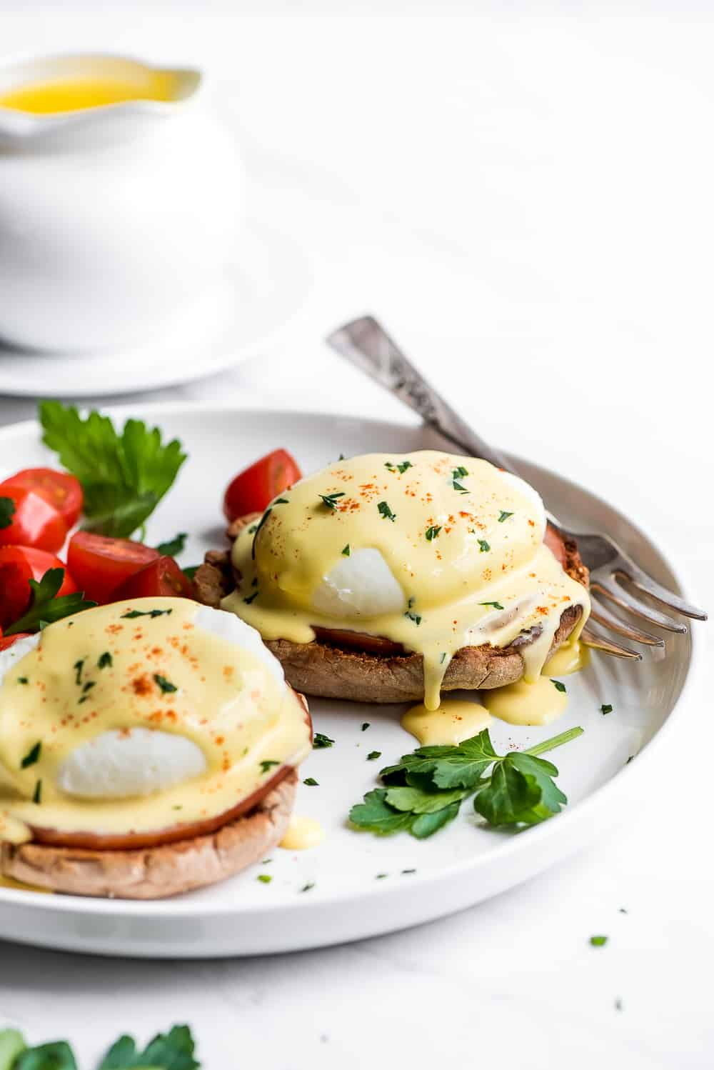Two Eggs Benedict on a plate with hollandaise dripping off of them.