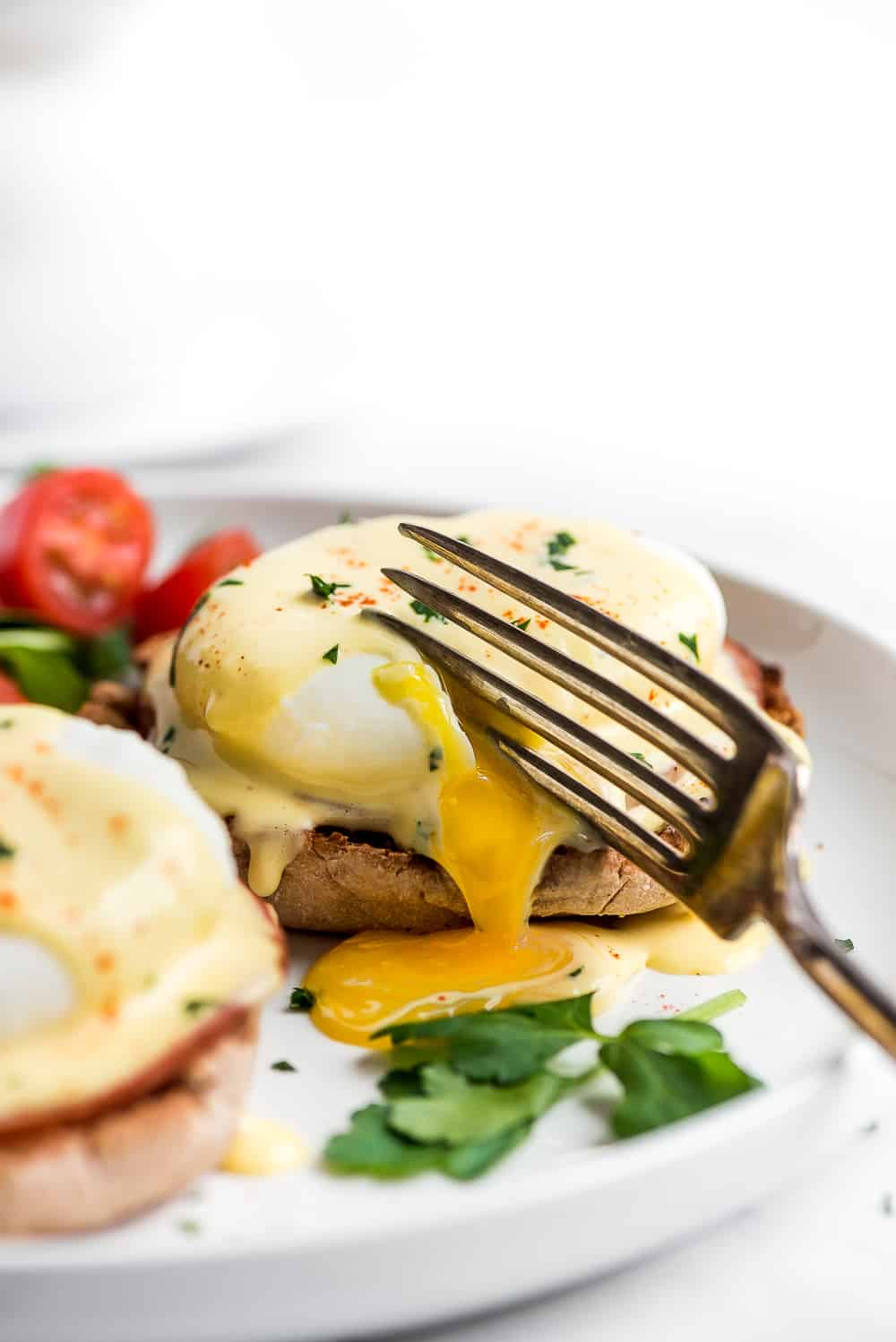 Egg Benedict on a plate being cut into with a fork.