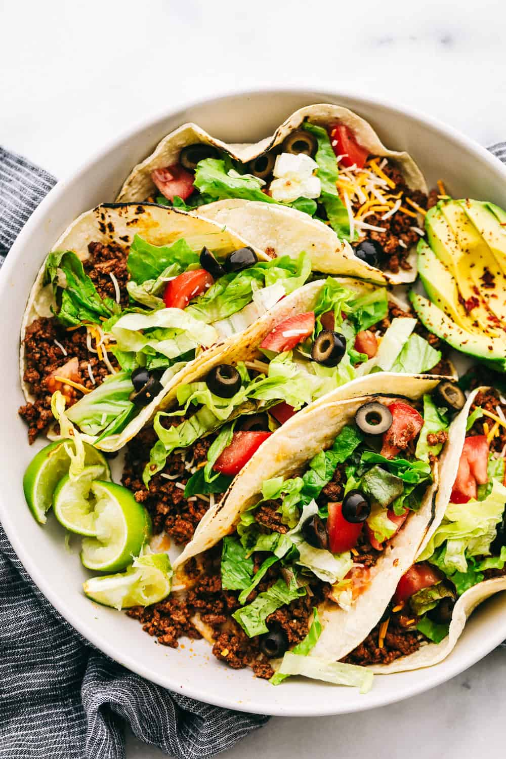 Five beef tacos on a plate loaded with shredded lettuce, sliced black olives, shredded cheese, tomato slices with lime slices and an avocado sliced on the side.