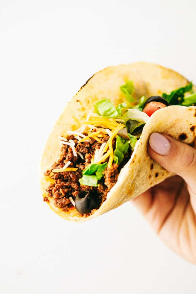 A beef taco with olives, shredded lettuce and shredded cheese being held up with the recipe critic hand.
