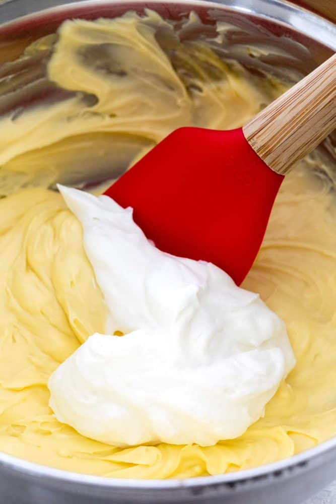 Spatula mixing eggs with cream in a bowl