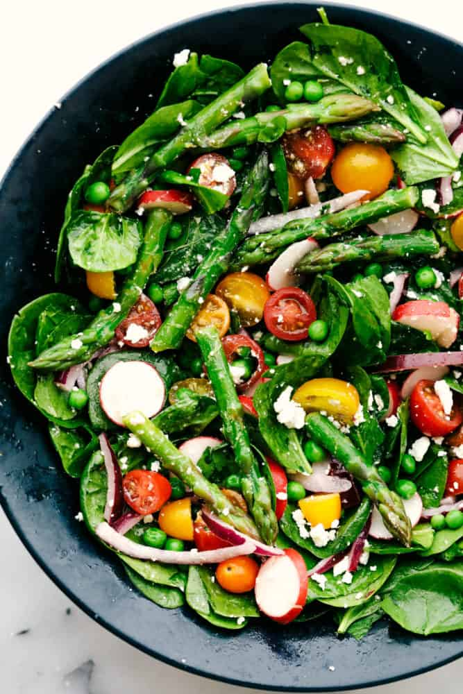 Asparagus salad with tomatoes, radish and spinach in a black bowl.