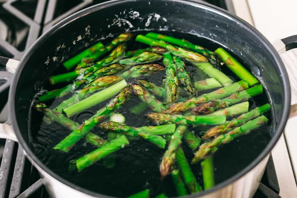 Asparagus cooking in boiling water on a gas stove top.