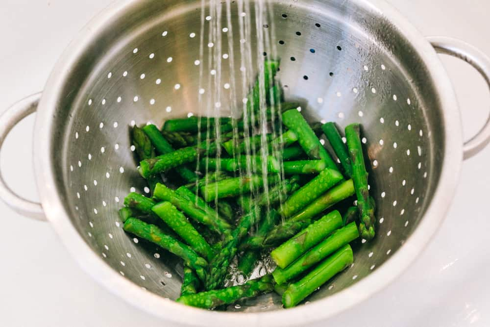Asparagus being washed with cold water in a strainer.