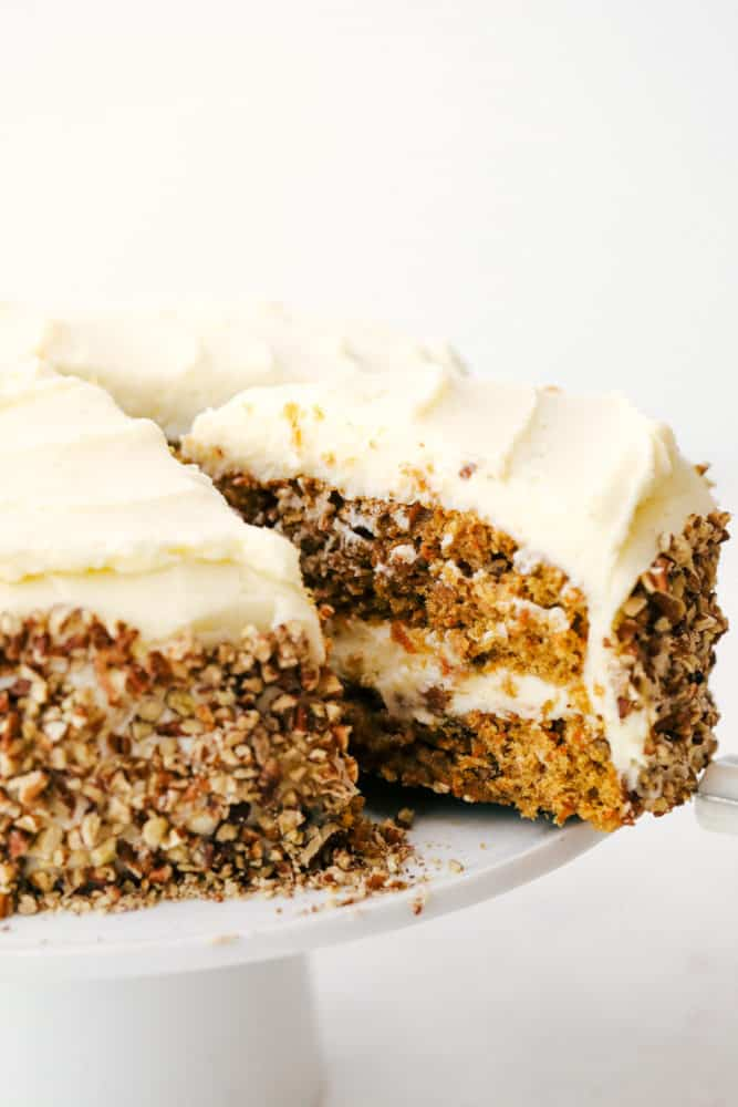 Carrot cake sliced and being pulled away from the cake platter.
