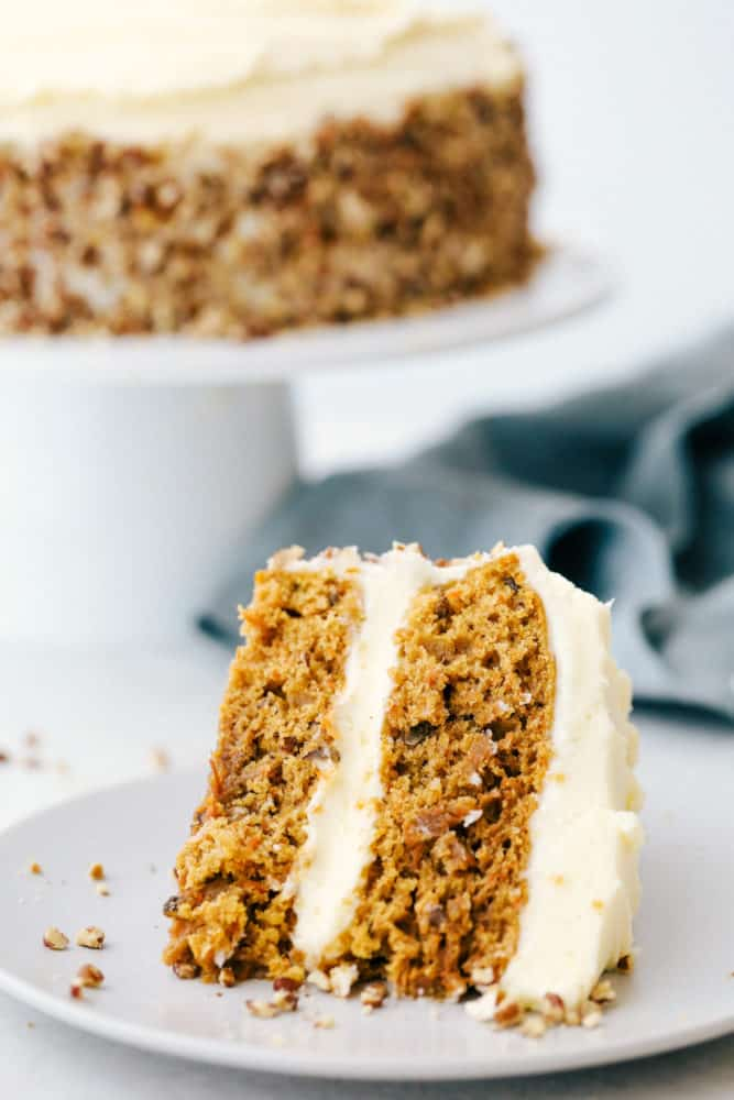 A slice of carrot cake on a plate with the carrot cake in the background on a cake platter.