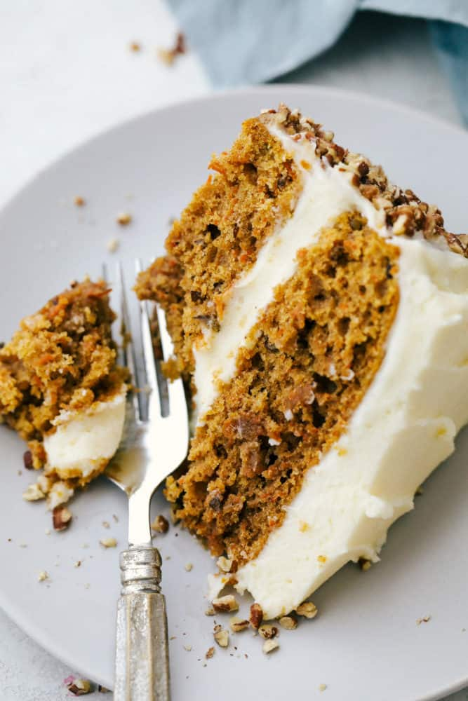 Carrot cake on a plate with a fork cutting off a bite.