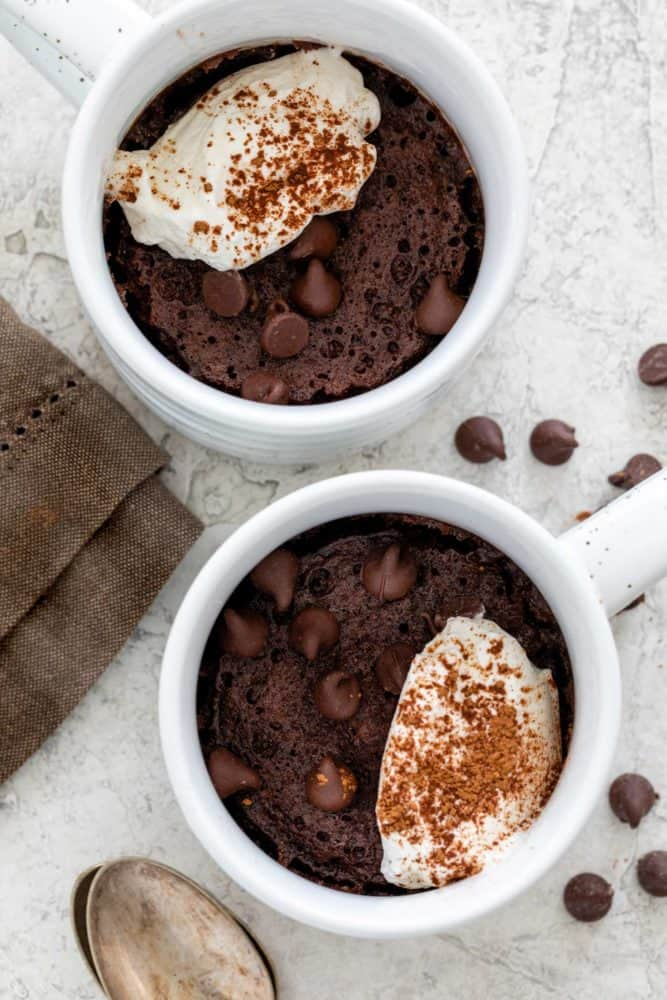 Two chocolate mug cakes topped with frosting