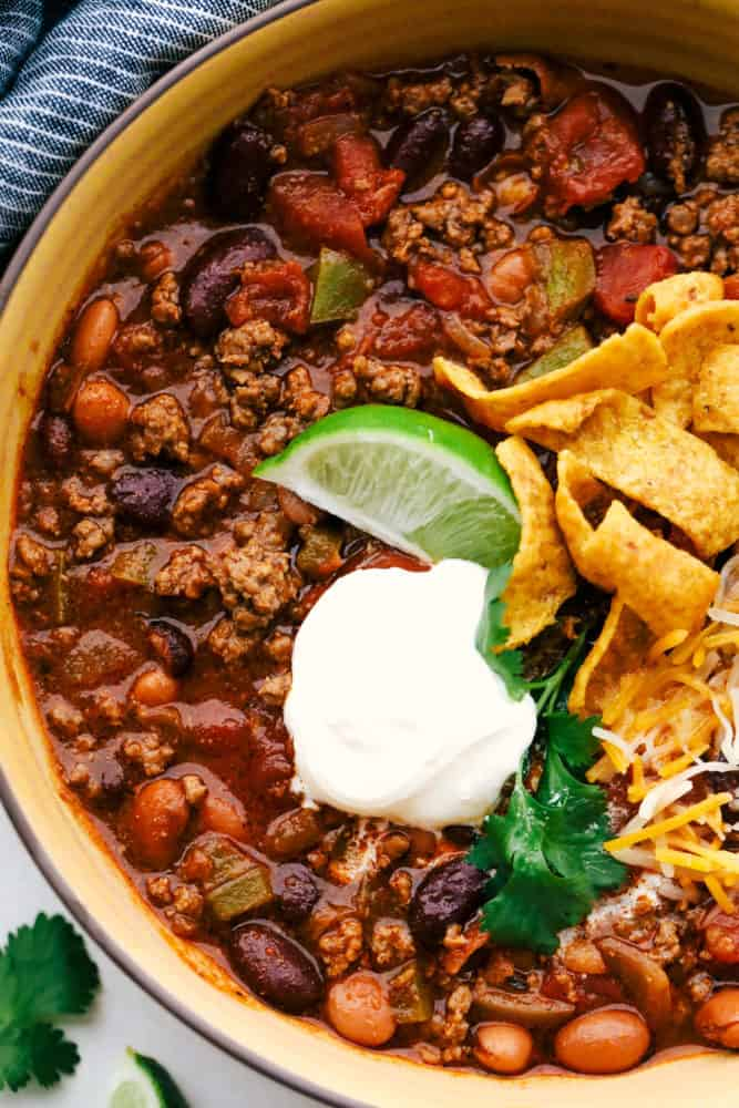 Chili in a bowl with lime wedge, sour cream, Frito chips and shredded cheese.