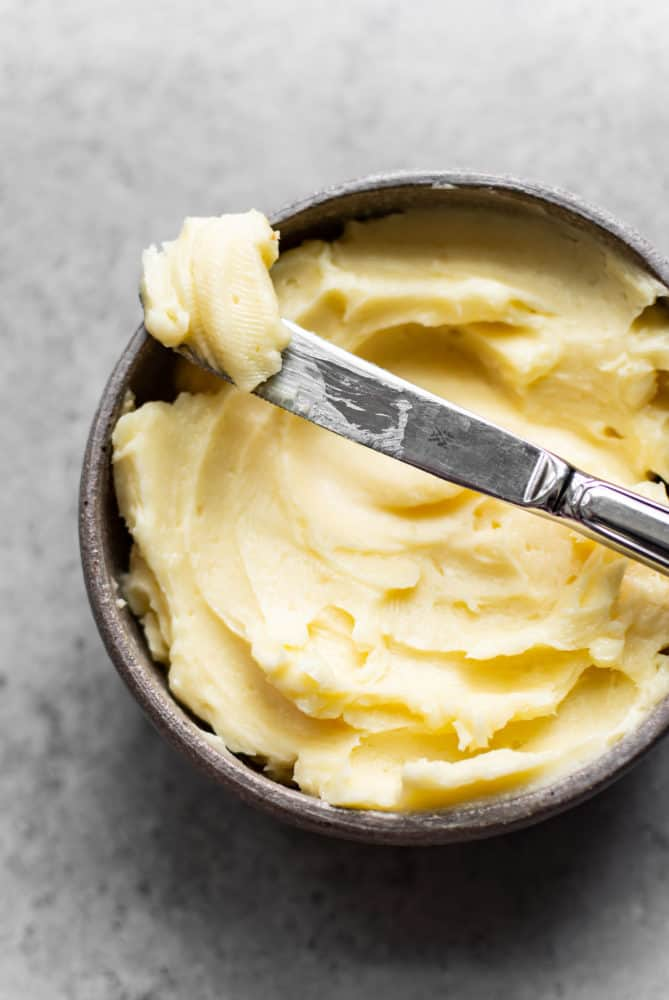 Honey butter in a bowl with a knife laying on top.