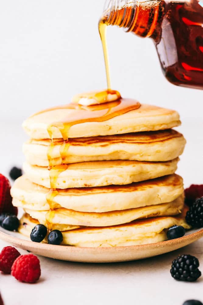 A stack of 6 pancakes with syrup being poured over top of butter and fresh berries.