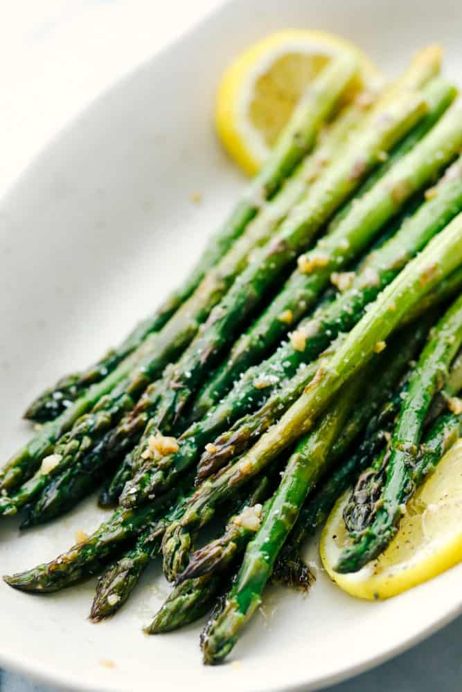 Asparagus placed on a white plate with lemon garnished throughout.