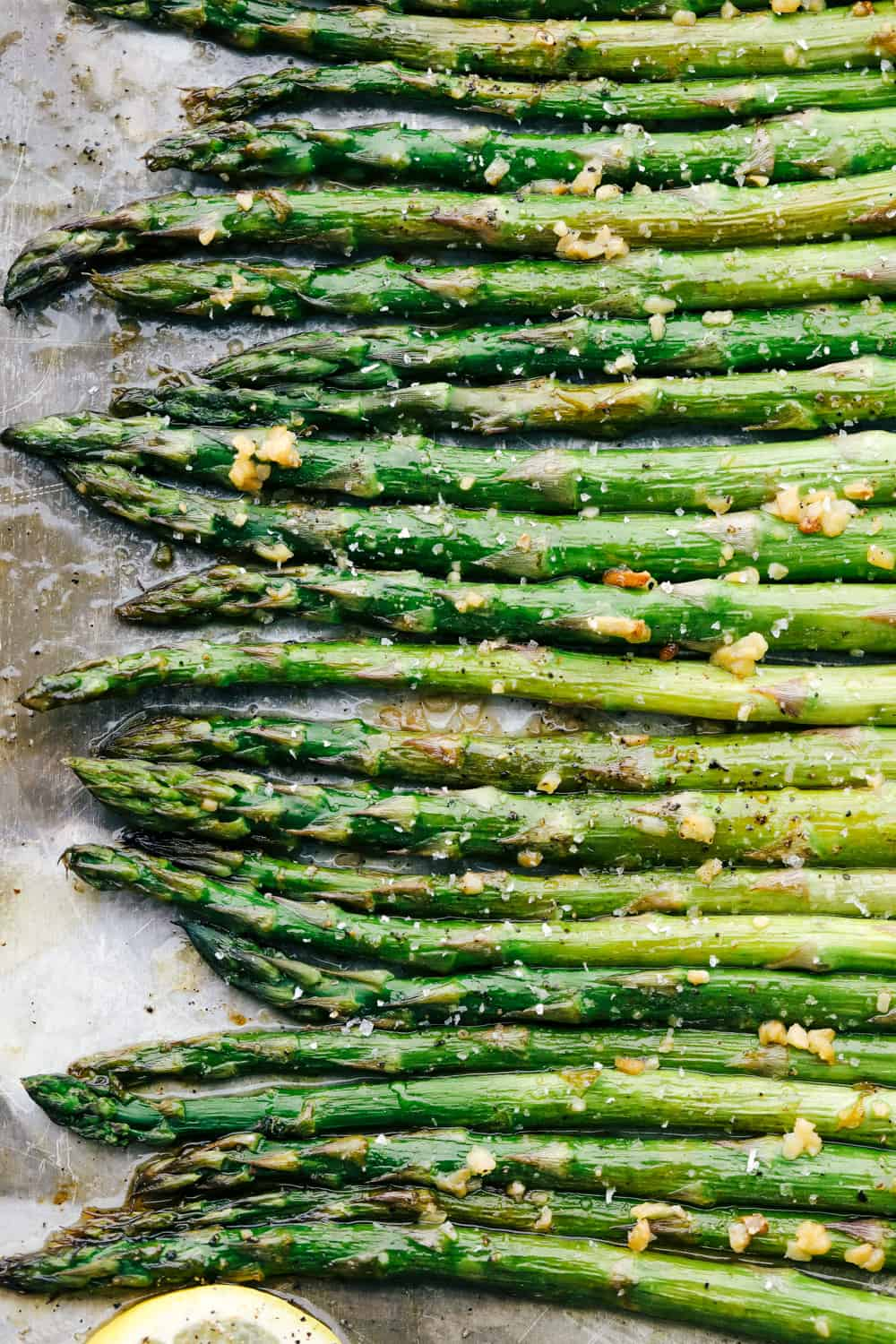 Asparagus laying flat on a baking sheet showing just he heads of the asparagus.