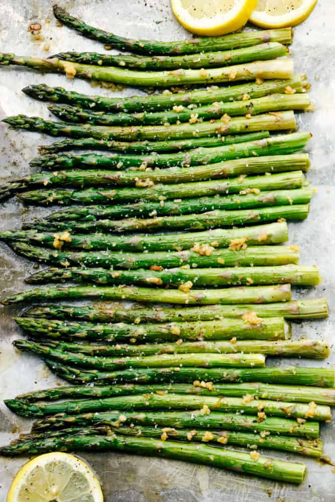 Asparagus all lined up flat on the baking sheet with lemons garnished around them.