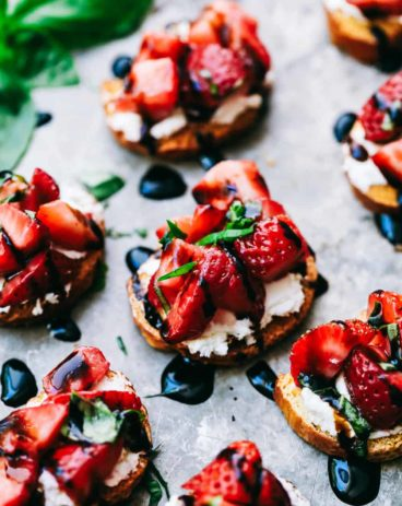 Strawberry bruschetta on a plate with balsamic dressing drizzled overtop.