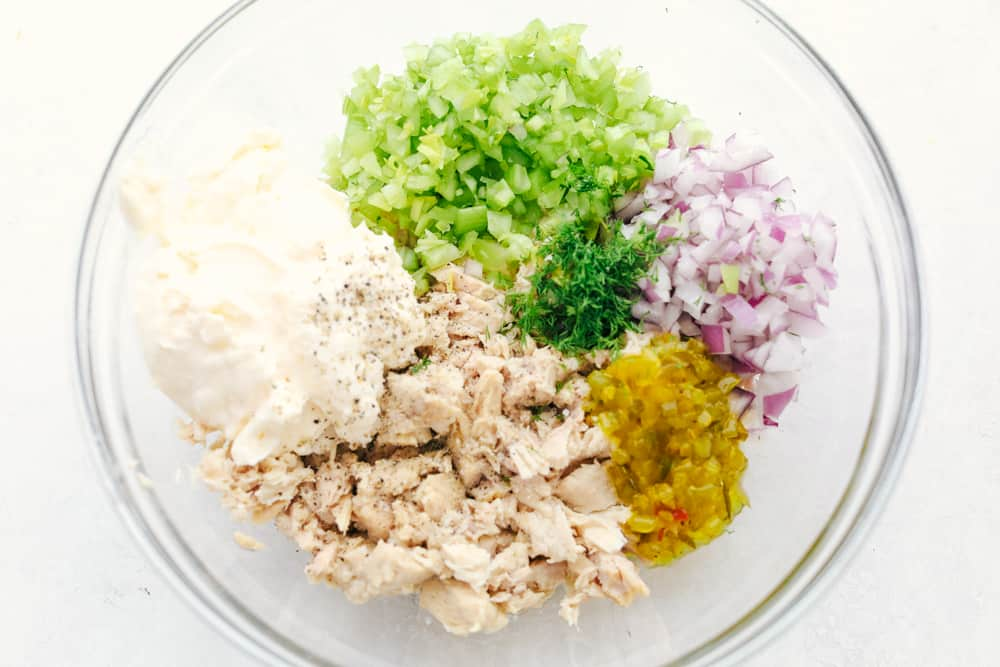 Tuna salad ingredients all separated in sections in the bowl.