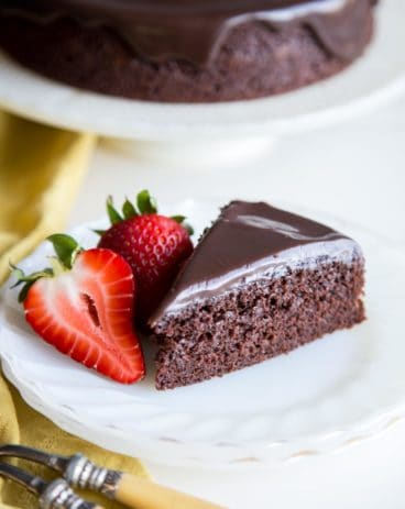 A slice of chocolate cake on a plate with strawberries