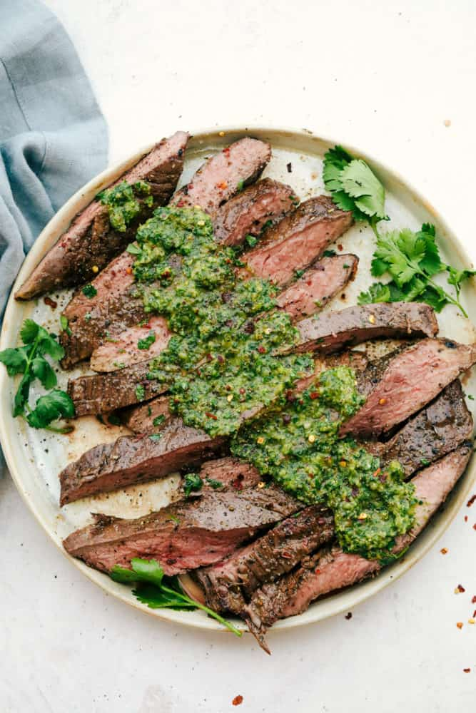 Flank steak sliced against the grain with chimichurri sauce on top on a white plate.