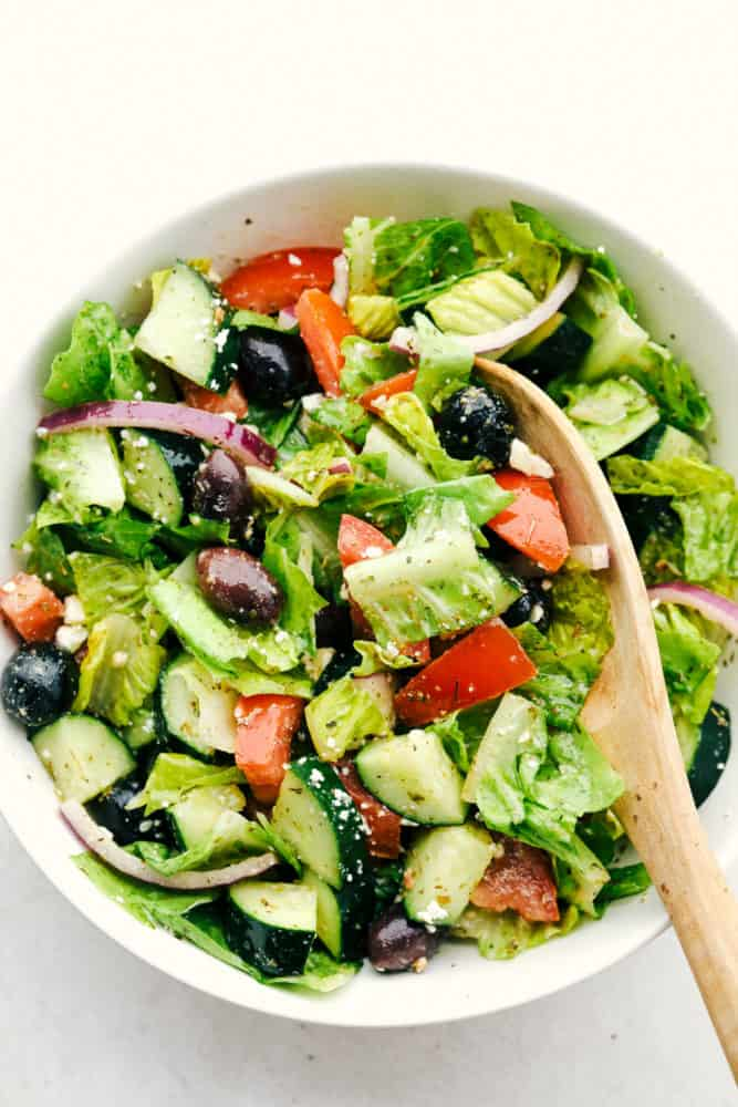 Greek salad in a white bowl with a wooden spoon.